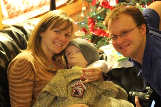 Megan and David Mathis holding Henryk with his Christmas gift ornament (Baby's First Christmas)
